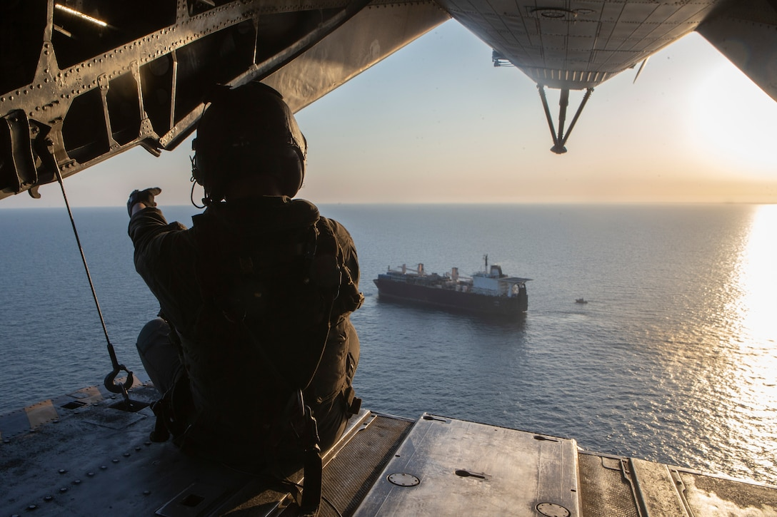 A U.S. Marine sits on the CH-53E Super Stallion's ramp as the aircraft leaves the USNS D. T. Williams (T-AK-3009), April 5.