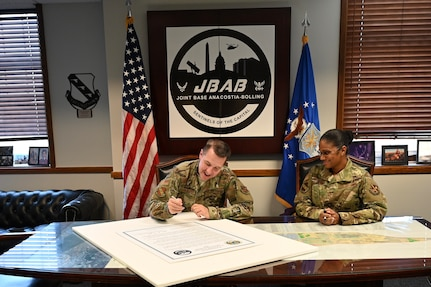U.S. Air Force Col. Michael Zuhlsdorf, Joint Base Anacostia-Bolling and 11th Wing commander, signs the Sexual Assault Awareness and Prevention Month Proclamation as Joint Base Anacostia-Bolling Command Chief Master Sgt. Christy Peterson looks on at Joint Base Anacostia-Bolling, Washington DC, April 5, 2021. The Sexual Assault Prevention and Response team on Joint Base Anacostia-Bolling provides victim support and resources, civilian and military training, and community awareness. Sexual Assault Awareness and Prevention Month is commemorated every April, and annual events are organized by the SAPR office. This year's events include a virtual fun run, a calendar of daily reflections, and a proclamation signed by 11WG leadership, which will travel throughout the installation where passersby may add their signatures and support. (U.S. Air Force  photo by Technical Sgt. Katie Edelman)