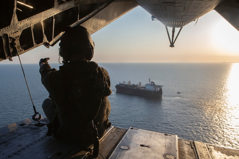 A Marine looks out from the ramp of a helicopter.
