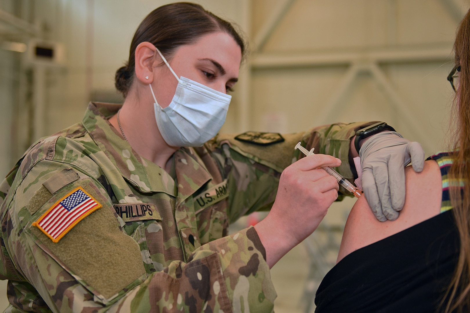 Specialist Jennifer Phillips, a combat medic with the Michigan Army National Guard's Task Force Red Lion COVID-19 vaccination/testing team, administers the vaccination to employees and their families during a walk-in clinic for the Army Tank-Automotive and Armaments Command in Warren, Michigan, April 28, 2021.