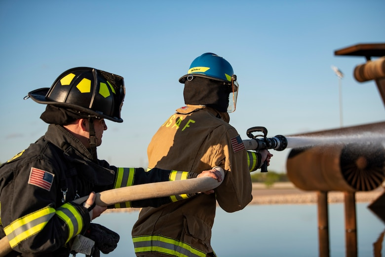 Senior Airman Jarrett Ziegler, 512th Civil Engineer Squadron firefighter, left, and Airman 1st Class Andrew Trujillo, 7th CES firefighter, test a firehose at Dyess Air Force Base, Texas, May 4, 2021. Zieglar and Trujillo conducted a routine function test of the firehose to ensure it was operating properly before conducting an aircraft fire training. (U.S. Air Force photo by Airman 1st Class Colin Hollowell)