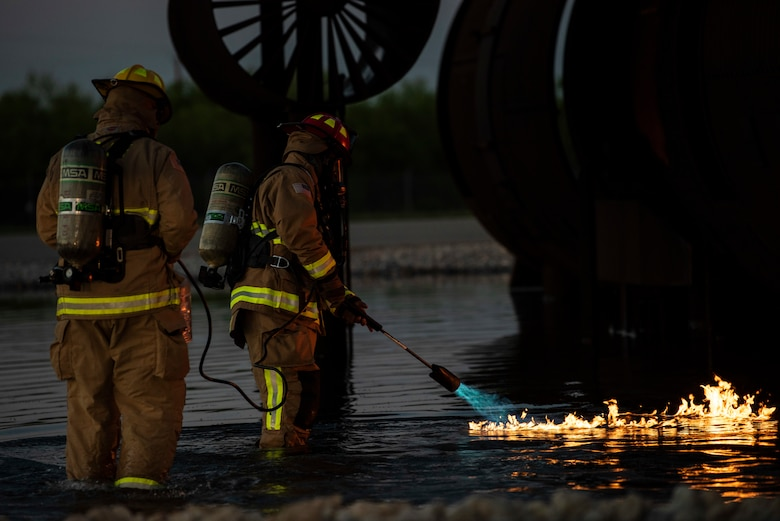 Two firefighters assigned to the 7th Civil Engineer Squadron ignite a fire during a nighttime aircraft fire training at Dyess Air Force Base, Texas, May 4, 2021. During the live fire training, a flammable gas was ignited on the surface of the water to simulate the pooling and burning of jet fuel around an aircraft. (U.S. Air Force photo by Airman 1st Class Colin Hollowell)