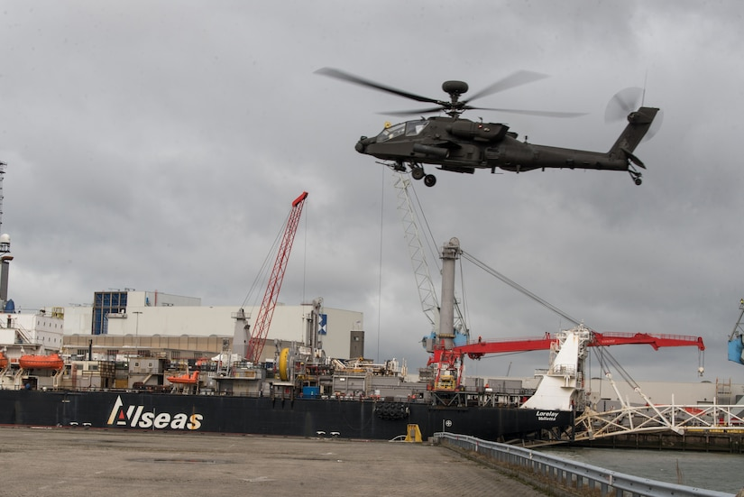 A helicopter flies over a port.