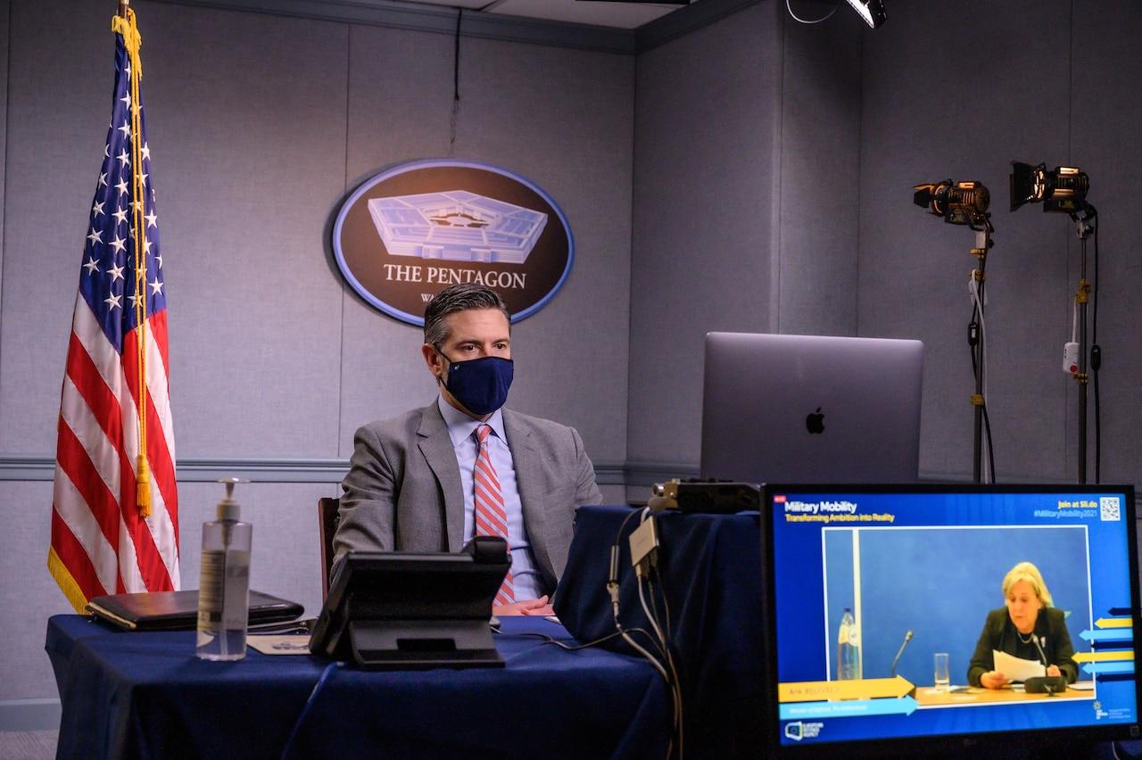 A man speaks at a virtual meeting.