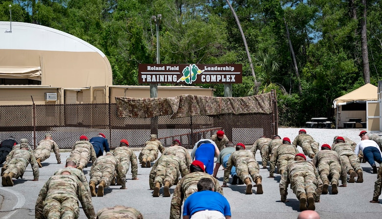 Special Tactics Airmen along with friends and family do memorial push-ups after a dedication ceremony at Hurlburt Field, Florida, May 6, 2021 i