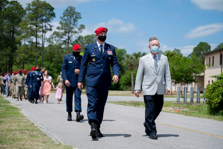 U.S. Air Force Col. Matthew Allen, the commander of the 24th Special Operations Wing, and U.S. Air Force, retired, Col. Mark Roland, father of U.S. Air Force Capt. Matthew Roland, walk to unveil a sign during a building dedication ceremony at Hurlburt Field, Florida, May 6, 2021.