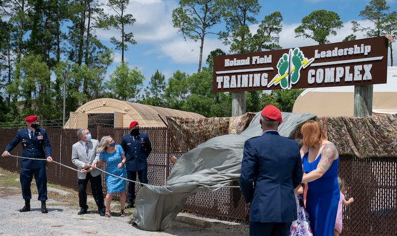 The family of U.S. Air Force Capt. Matthew Roland unveils a sign during a building dedication ceremony at Hurlburt Field, Florida, May 6, 2021. The Special Tactics Training Squadron facility was renamed in honor of Roland, a 23rd STS special tactics officer who died protecting his teammates during an ambush at an Afghan-led security checkpoint near Camp Antonik, Afghanistan, Aug. 26, 2015.