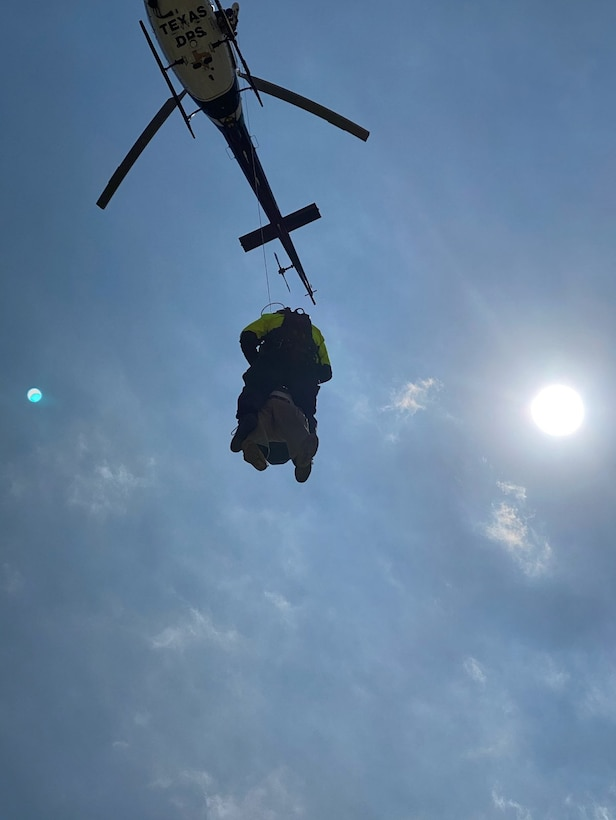Helicopter hoisting person into the air