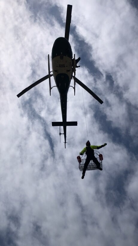 Helicopter hoists a person