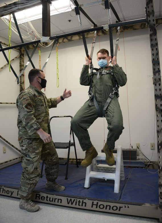 Master Sgt. John Maher, 414th Combat Training Squadron Red Flag section chief, Nellis Air Force Base, Nevada, trains former Ultimate Fighter Championship champion and UFC Hall of Famer Forrest Griffin emergency parachute use prior to his flight with the U.S. Air Force Thunderbirds at Nellis Air Force Base, Nevada, Apr. 2021.