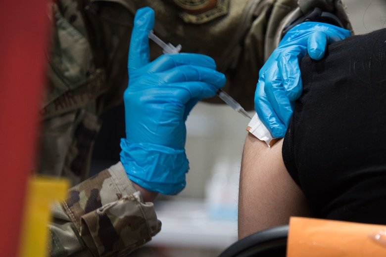U.S. Air Force Senior Airman Daschia Lawrence, 92nd Healthcare Operation Squadron medical technician, administers a COVID-19 vaccine to a community member