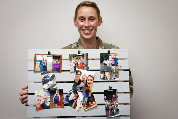 Female Airman hold decorative pallet board with photos of her children attached.