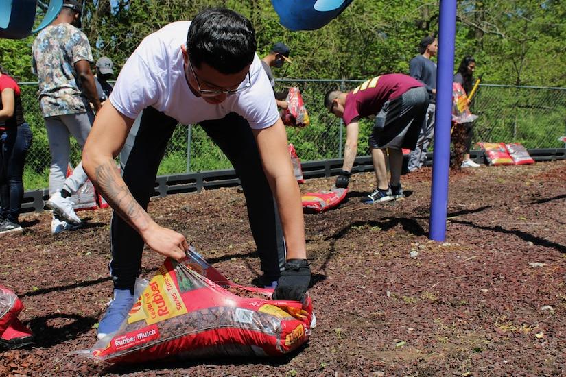 volunteer soldier opens bag of mulch