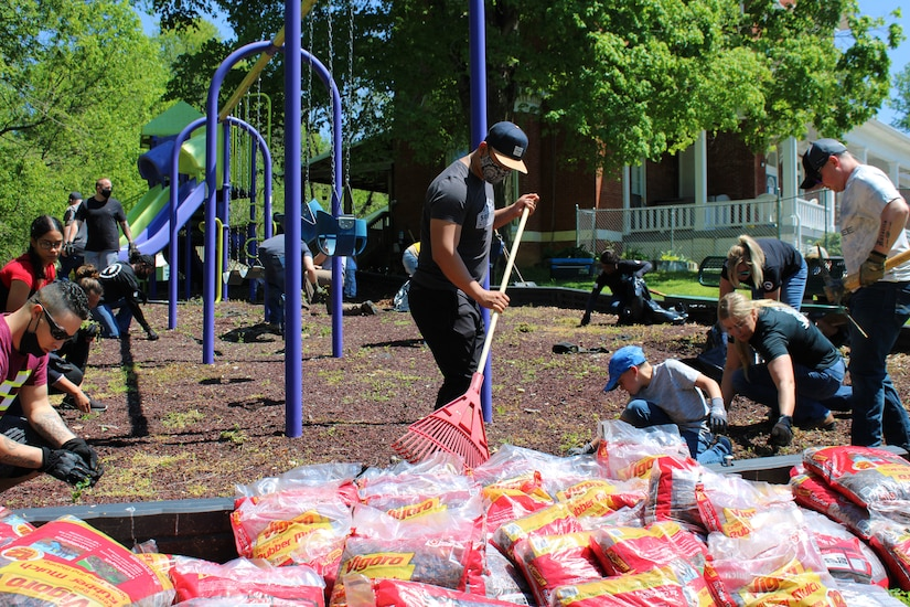 volunteer soldier rakes mulch