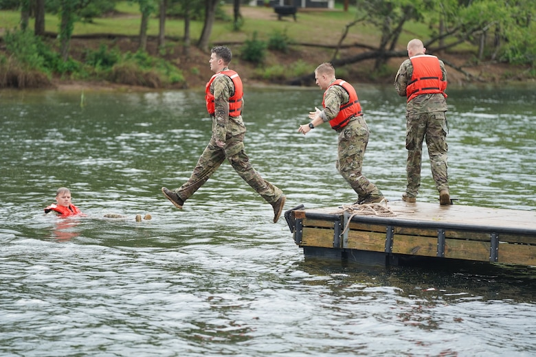 Competitors step off a lake dock into water