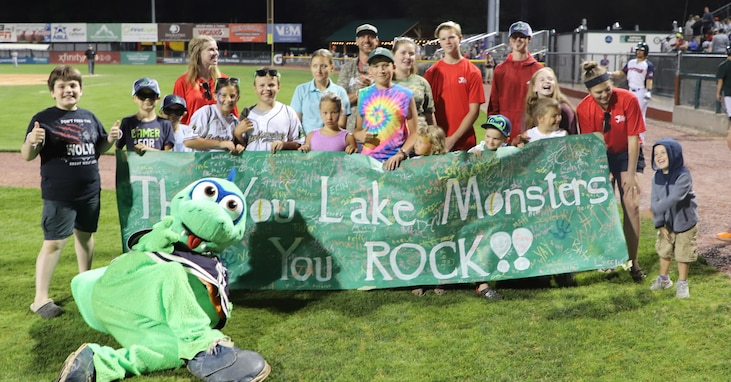 Children holding banner with Lake Monster Mascot