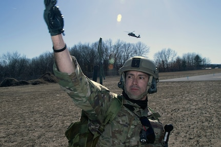 Senior Airman Ivan Villavicencio, of the 104th Security Forces Squadron, signals to responders as a medical helicopter approaches during a joint training exercise between the Massachusetts Air and Army National Guard on March 12, 2021, at Barnes Air National Guard Base, Mass.