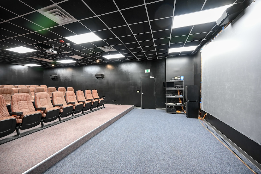 Stadium-style seating and a big screen inside the theater room of the Airman Recreation Center.