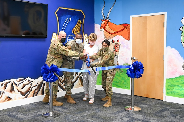 Members of the military and community cut a ceremonial ribbon.