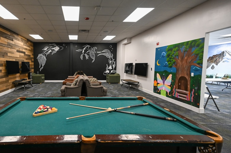 Painted walls of coy fish and a fairy adorn the walls of a recreation room with big-screen TVs and a pool table inside the Airman Recreation Center.