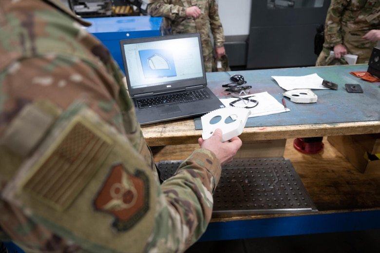Maj. Gen. Mark Weatherington, the 8th Air Force and Joint-Global Strike Operations Center commander, inspects a 3D printed B-1B Lancer part during his visit to Ellsworth Air Force Base, S.D., May 4, 2021.