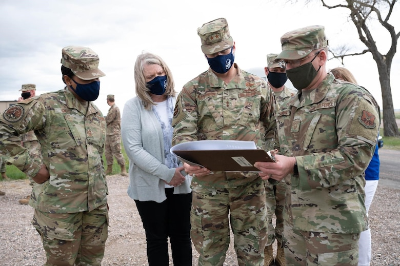 Maj. Gen. Mark Weatherington, 8th Air Force and Joint-Global Strike Operations Center commander, second from right, and Chief Master Sgt. Melvina Smith, 8th Air Force command chief and J-GSOC senior enlisted leader, far left, look over new construction plans for Camp Lancer during their visit to Ellsworth Air Force Base, S.D., May 4, 2021.