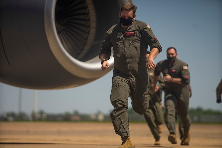U.S. Air Force Senior Airman Seth Amiott, a 50th Air Refueling Squadron boom operator, followed by crew members, runs toward a KC-135 Stratotanker aircraft during a simulated alert scenario April 21, 2021, at Barksdale Air Force Base, Louisiana. The crew executed an alert drill during an integrated training event, meant to test timing and efficiency in an emergency takeoff scenario.