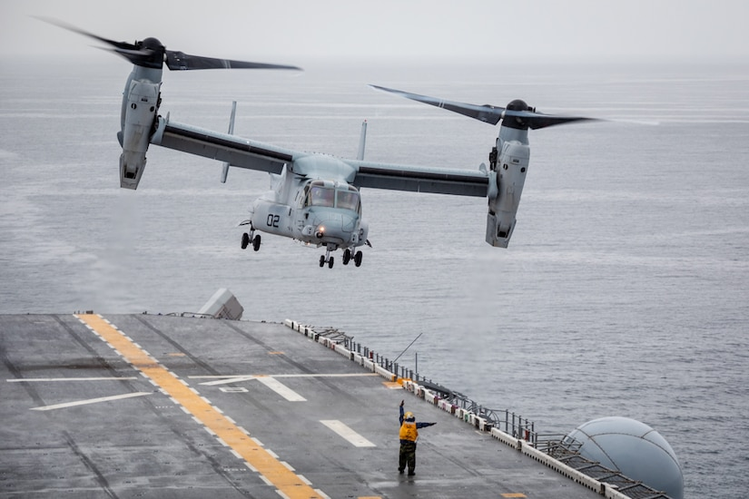 A sailor signals to an aircraft before it lands on a ship at sea.