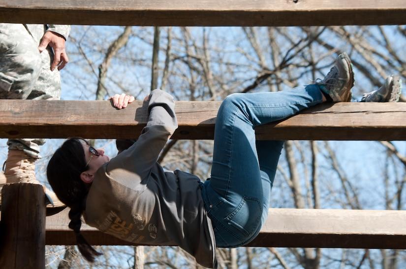 A woman hangs from a wooden bar.