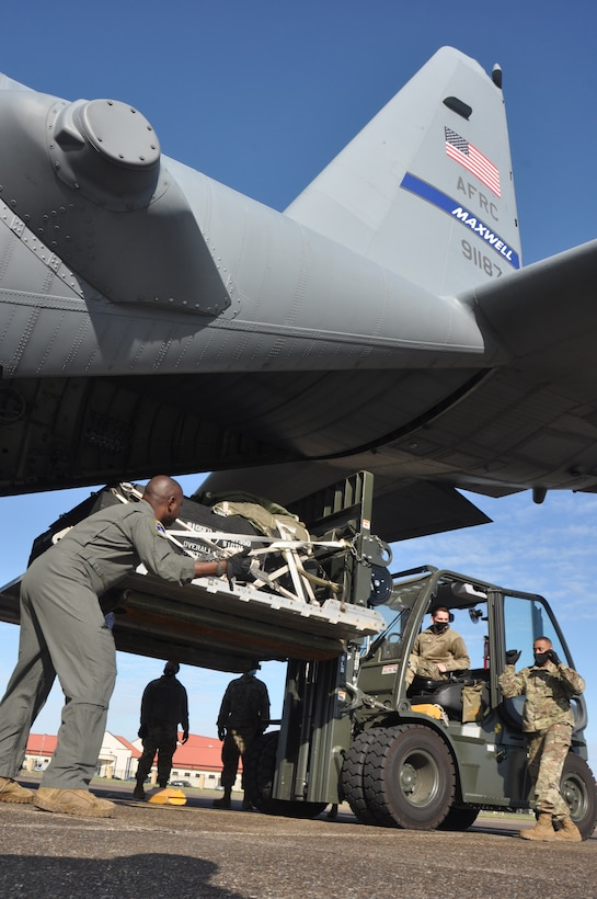 service members load cargo on an aircraft