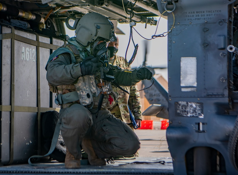 Airman performs pre-flight checks on a helicopter.
