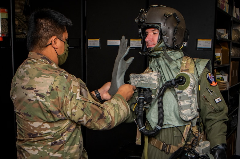 Airman assists another Airman fitting his CBRN flight gear.