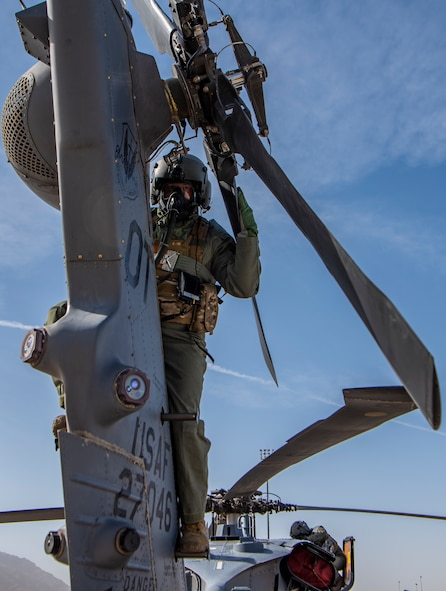 Airmen perform pre-flight checks on a helicopter.