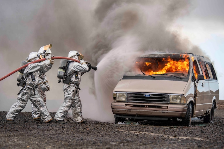 Two Marines use a hose to spray water onto a vehicle fire.