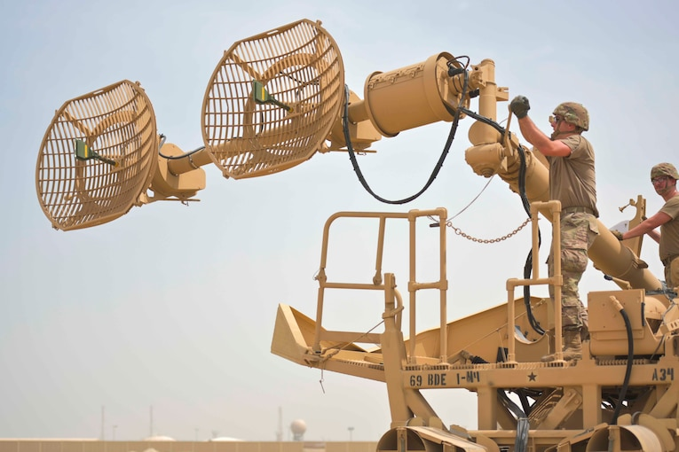 A soldier cranks open a large antenna.