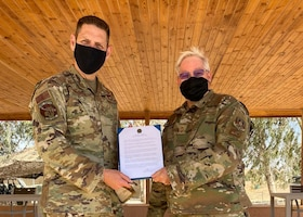 U.S. Air Force Brig. Gen. Joseph Kunkel, the commander of the 332nd Air Expeditionary Wing, presents a proclamation naming April 25, 2021, Chief Master Sgt. David Purtee day at the wing in honor of him crossing 40-years of service. Purtee is assigned to the 121st Air Refueling Wing in Columbus, Ohio, and is currently deployed to the wing at an undisclosed location in the Middle East. (Photo courtesy Chief Master Sgt. Jeff Vander Woude)