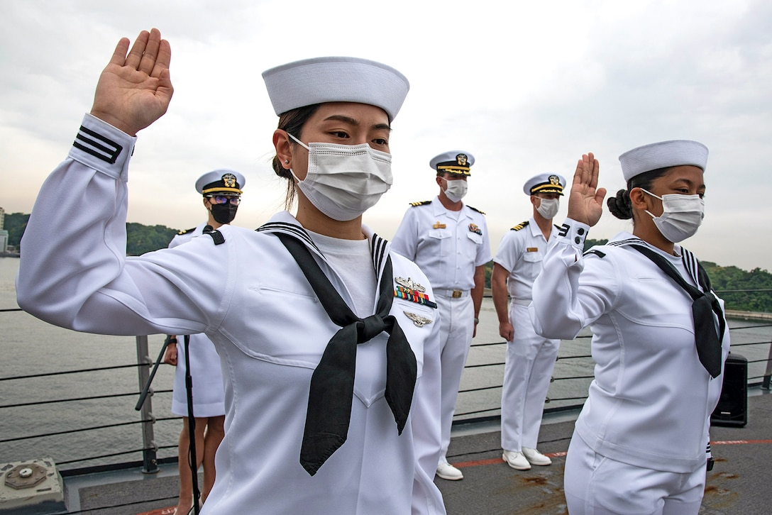 Two sailors stand with right hands raised aboard a ship's deck.