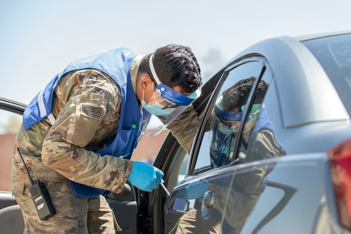 A soldier wearing protective medical gear leans into a car's open driver's side window.