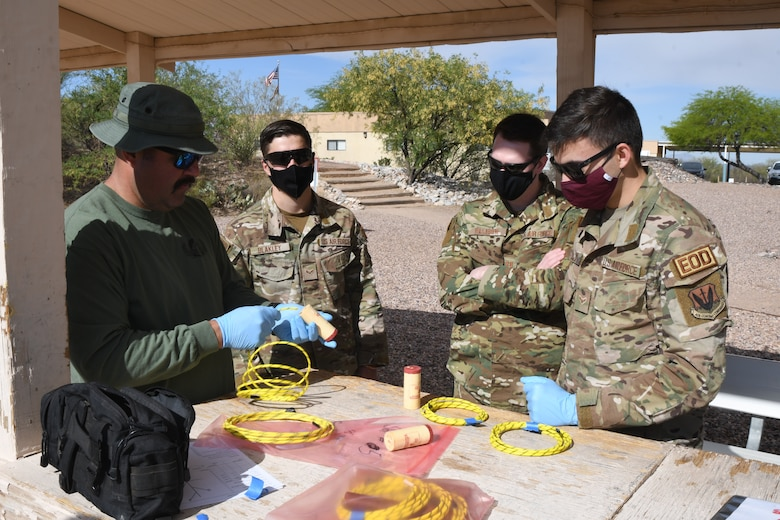 A picture of Airman and a member of the Tucson Bomb Squad preparing explosives for demolition training
