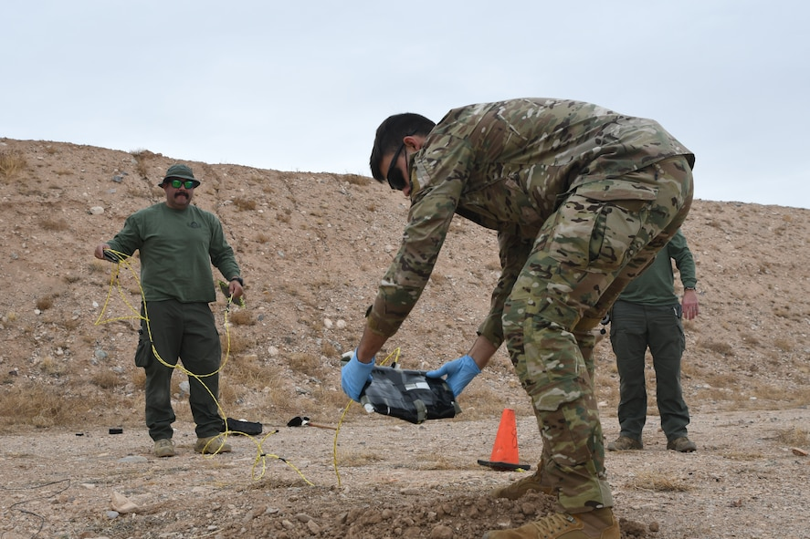 A picture of an Airman planting an explosive.