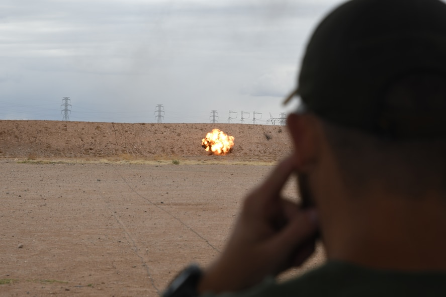 A picture of a man watching a detonation.