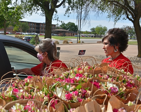Volunteers from a local business distribute flowers to military spouses during the Military Spouse Appreciation Day Drive-Thru event at the Event Center on Goodfellow Air Force Base, Texas, May 7, 2021. The 17th Force Support Squadron partnered with a local business to recognize military spouses. (U.S. Air Force photo by Senior Airman Ashley Thrash)
