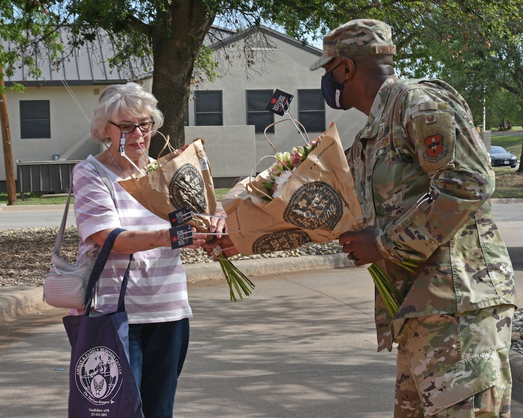 U.S. Air Force Col. James Finlayson, 17th Training Wing vice commander, gives flowers to Frauke Harrington, military retiree spouse, during the Military Spouse Appreciation Day Drive-Thru event at the Event Center on Goodfellow Air Force Base, Texas, May 7, 2021. Harrington's spouse retired from the Navy, Air Force, and Air National Guard. (U.S. Air Force photo by Senior Airman Ashley Thrash)