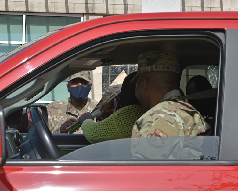 U.S. Air Force Col. James Finlayson, 17th Training Wing vice commander, hands flowers to Chief Master Sgt. Marcus Washington, 17th Medical Group superintendent, and his spouse, during the Military Spouse Appreciation Day Drive-Thru event at the Event Center on Goodfellow Air Force Base, Texas, May 7, 2021. Military spouse appreciation day gave thanks for the courage and strength of all military spouses. (U.S. Air Force photo by Senior Airman Ashley Thrash)