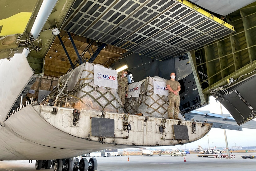 Service members stand by pallets of supplies in the back of an aircraft.