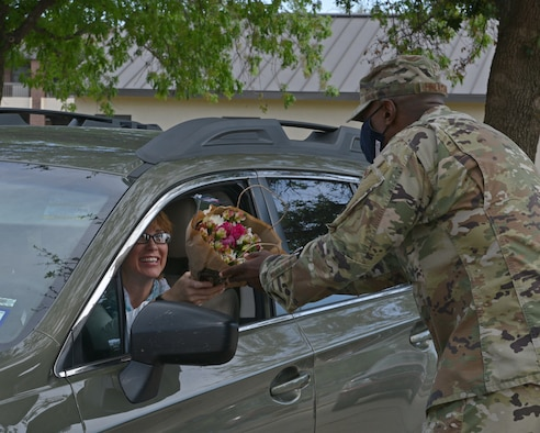 U.S. Air Force Col. James Finlayson, 17th Training Wing vice commander, hands flowers to a Goodfellow member during the Military Spouse Appreciation Day Drive-Thru event at the Event Center on Goodfellow Air Force Base, Texas, May 7, 2021. The base delivered over 800 flowers in support of all military spouses. (U.S. Air Force photo by Senior Airman Ashley Thrash)