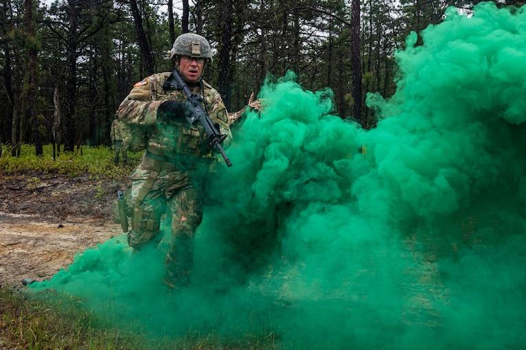 A guardsman runs through green smoke with a weapon.