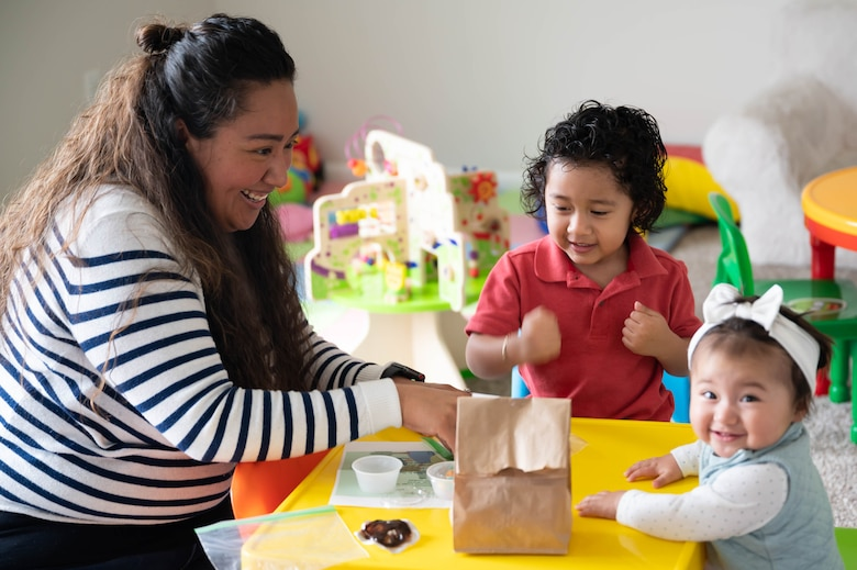 Iris Colon Salcido, left, stay-at-home mother and prospective Family Child Care provider, completes an Earth Day activity with her children three-year-old Luis Scalcedo, center, and 10-month-old Alessia Salcedo, April 22, 2021, at Malmstrom Air Force Base, Mont.