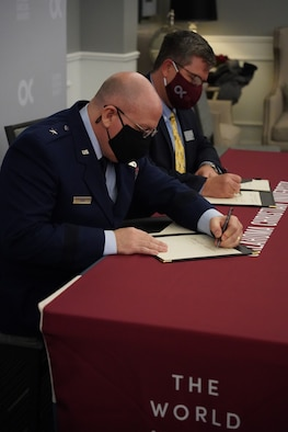 Two men signing papers