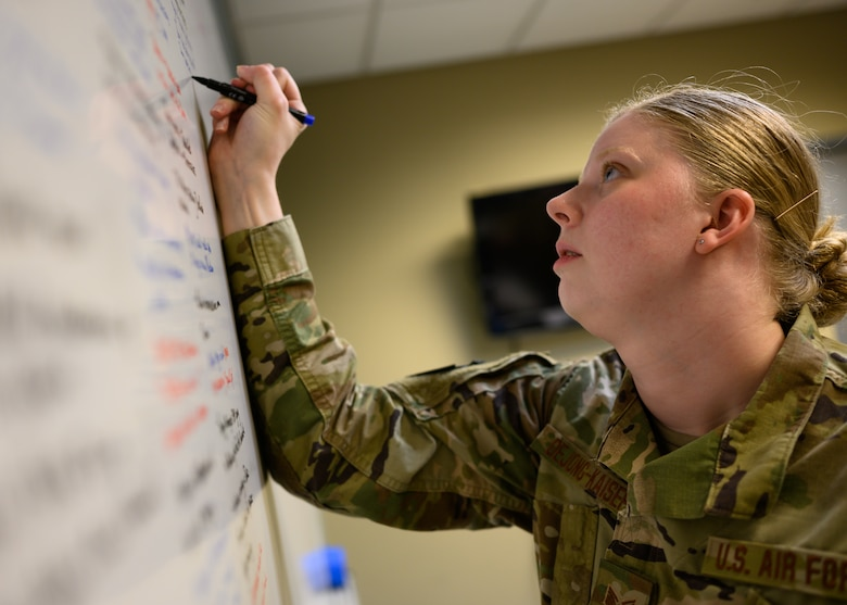 U.S. Air Force Staff Sgt. Gianna DeJong-Kaiser, an intelligence analyst for the 275th Cyberspace Operations Squadron, Maryland Air National Guard, lists out mission details on a whiteboard April 21, 2021, at the Gulfport Combat Readiness Training Center, Gulfport, Mississippi.